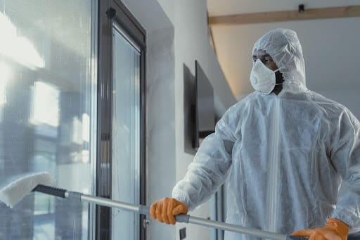 Worker with mask, gloves, and PPE on.