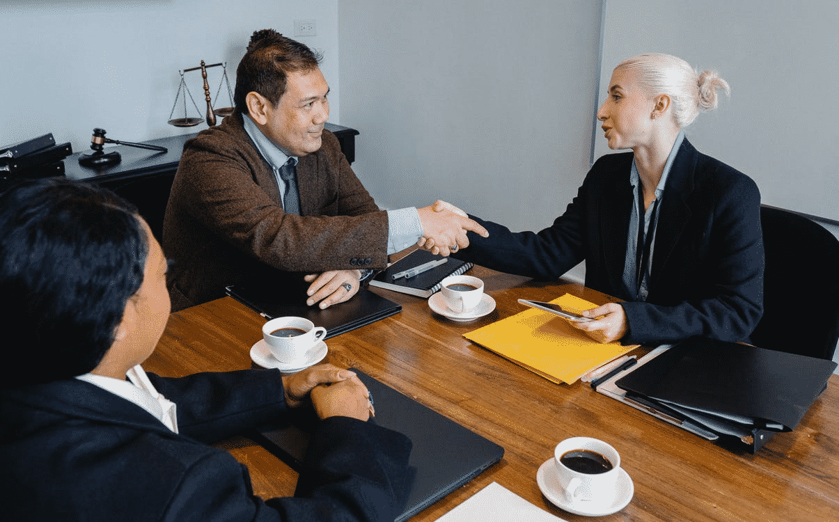 Three office workers in a meeting with two of them shaking hands.