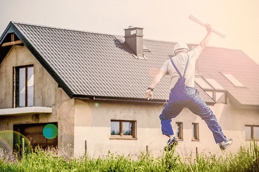 A construction worker in overalls and a hardhat jumping excitedly in front of a house.