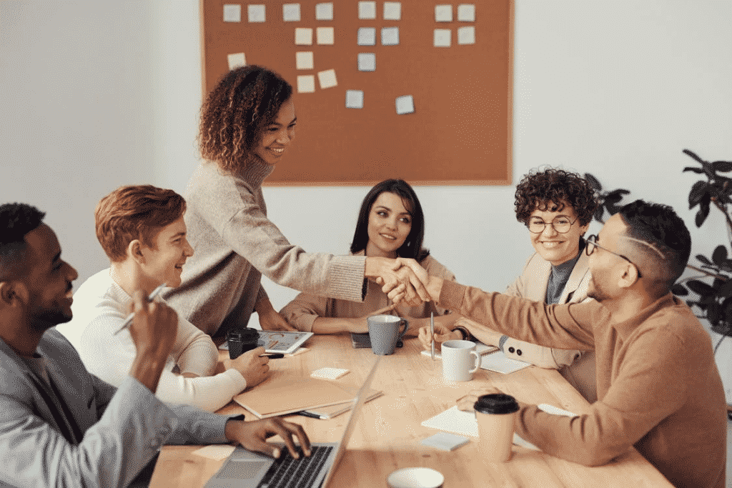 Six people in an office meeting with two people shaking hands.