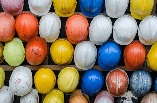 A wall of several multicolored construction hardhats.