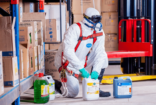 A worker in a hazmat suit handling bottles of chemicals in a warehouse.