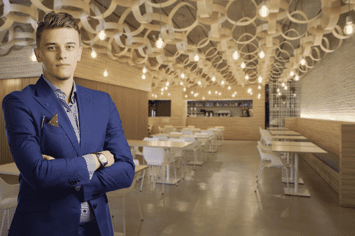 A restaurant manager in a blue suit looking at the camera with a large white dining hall in the background.